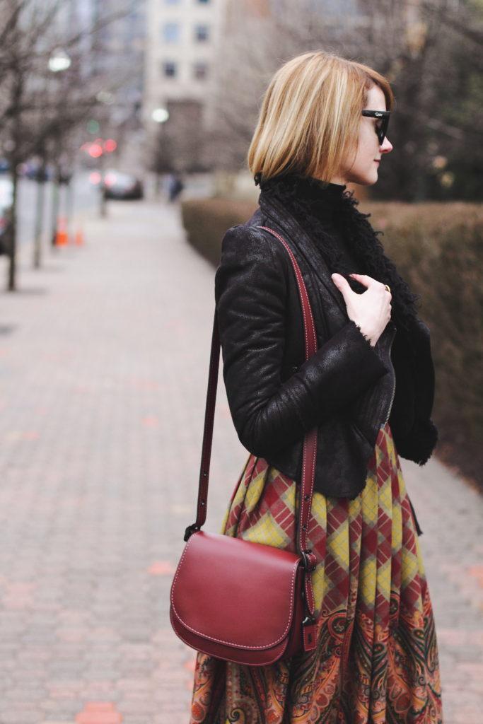 black turtleneck, leather jacket and Coach bag