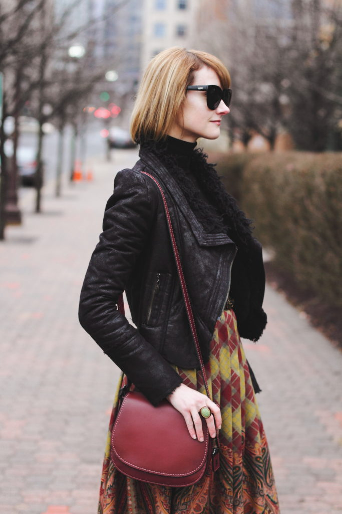 black turtleneck, leather jacket and Coach bag