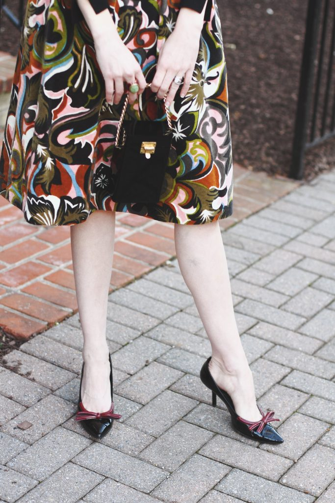vintage evening bag, print skirt, and Prada pumps