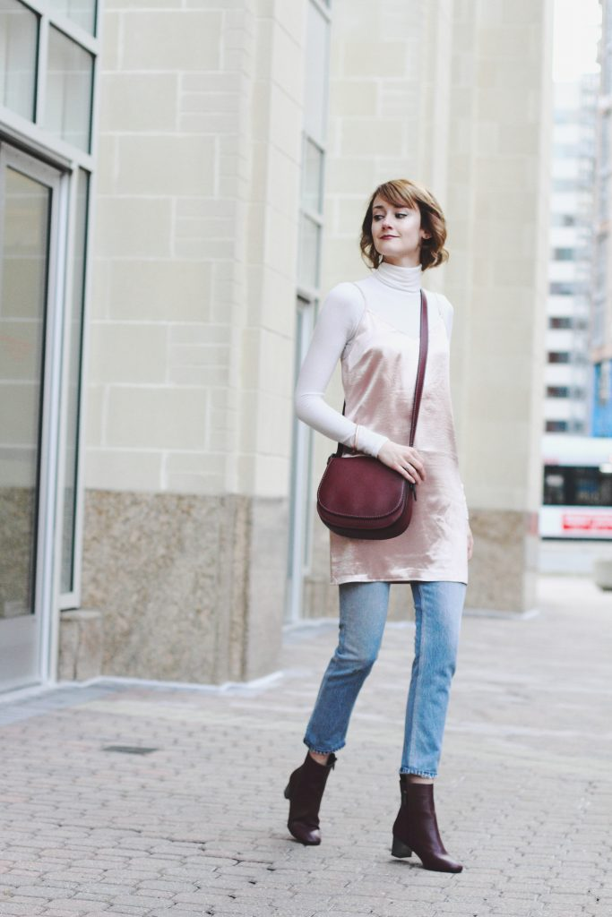 turtleneck, layering slip dress, jeans, and Coach bag