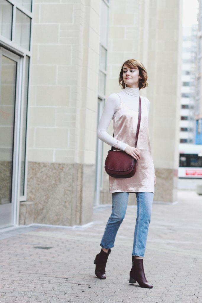 turtleneck, layering slip dress, jeans, and Coach bag