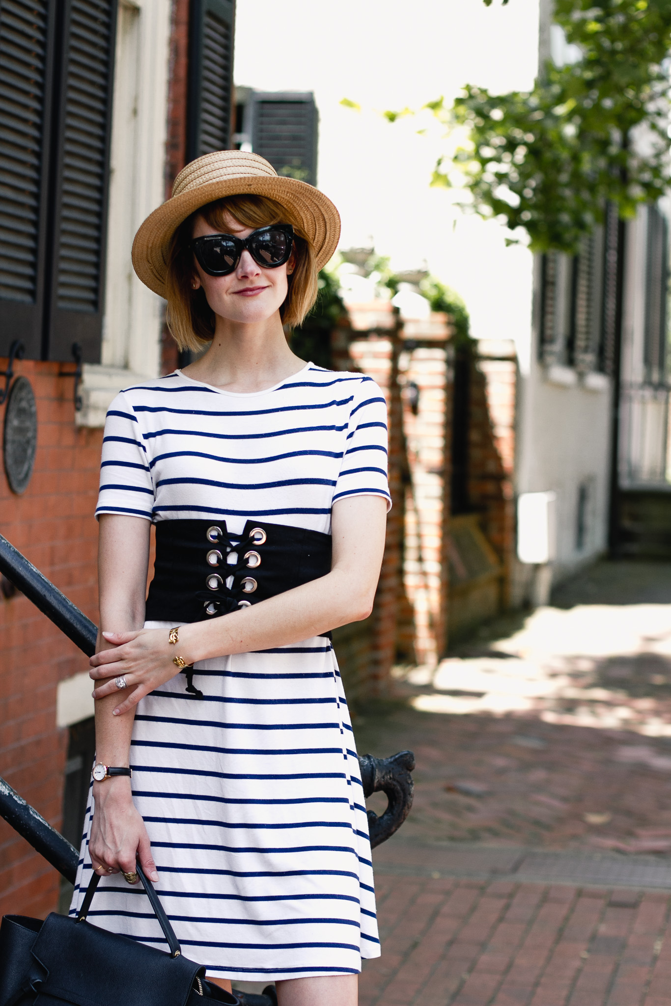 straw boater hat, striped dress, and corset belt