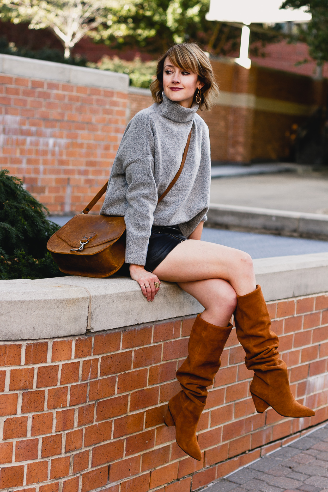 oversized sweater, leather skirt, and slouchy brown boots