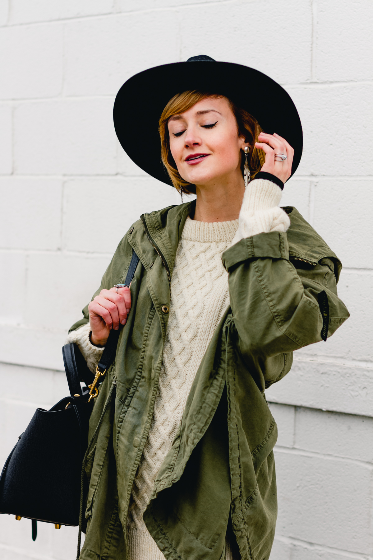 layered anorak, fisherman's knit, and black fedora