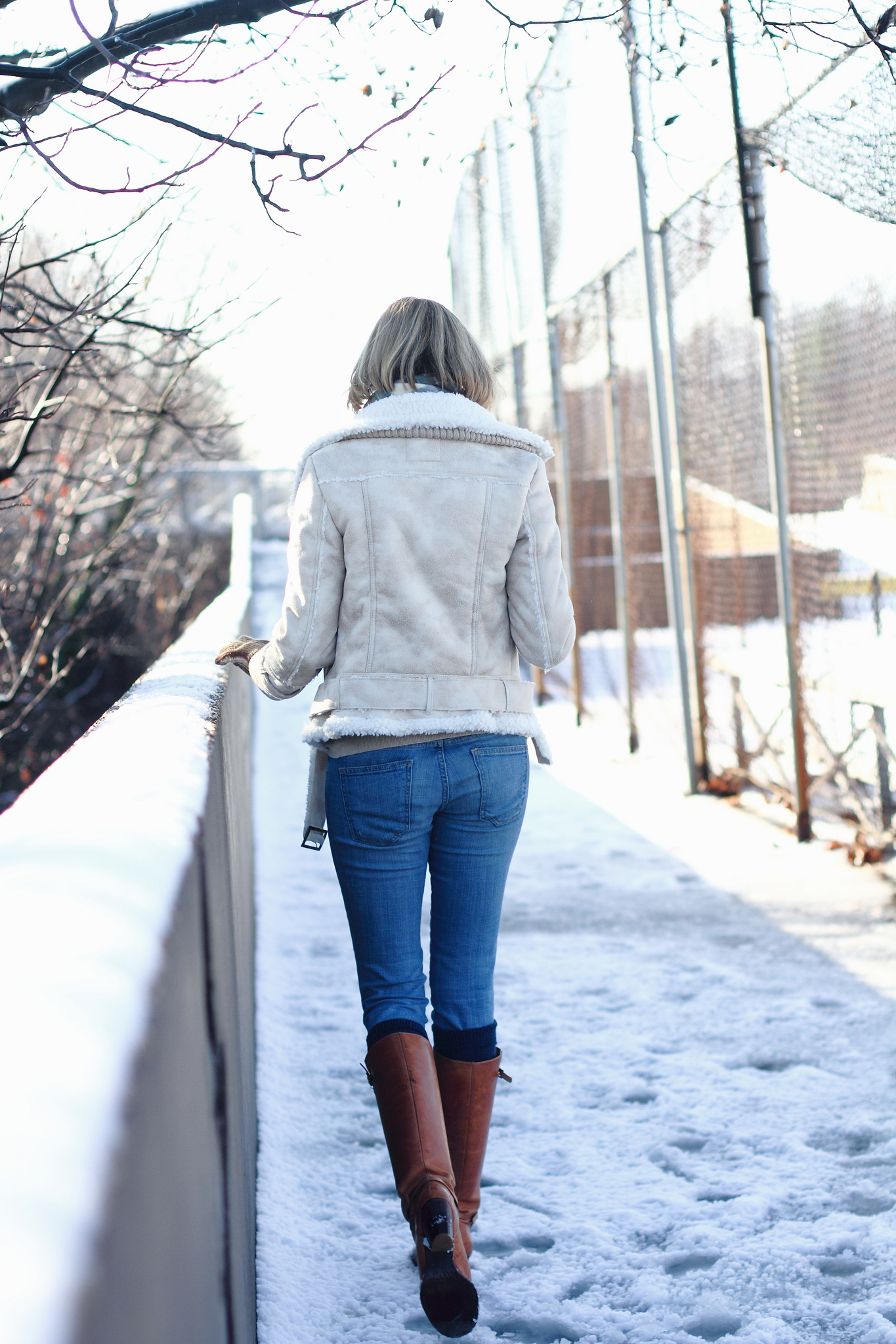 white shearling jacket and brown knee-high boots