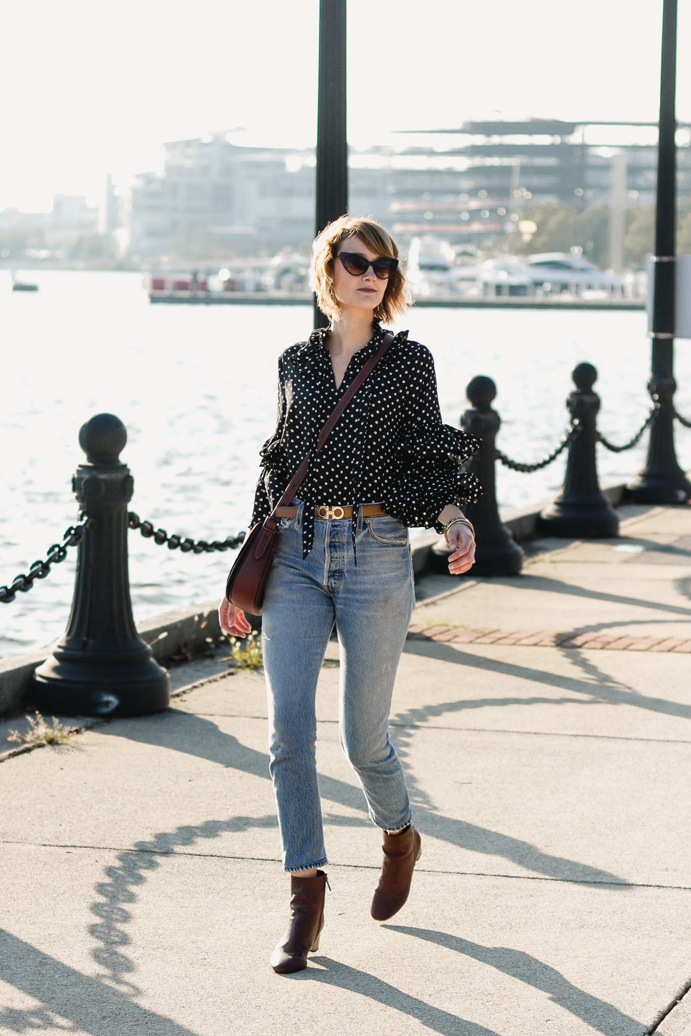 ruffled polka dot top, Ferragamo belt, and Re/Done jeans